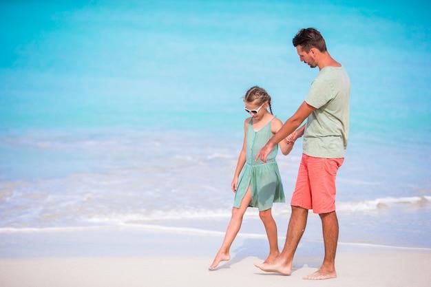 Padre feliz y su pequeña hija adorable en la playa tropical caminando juntos