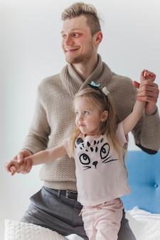Padre feliz sujetando los brazos de su hija