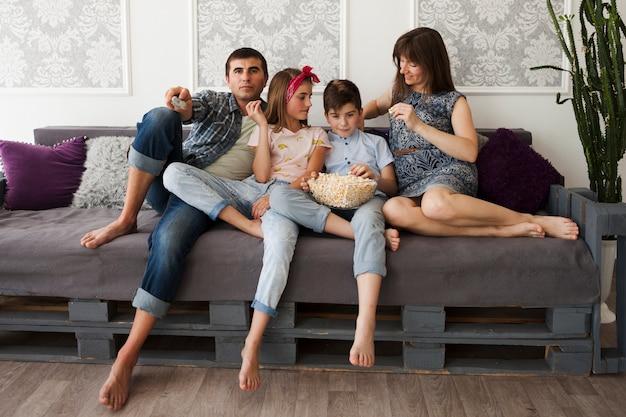 Padre feliz con sus hijos sentados en el sofá y comiendo palomitas de maíz