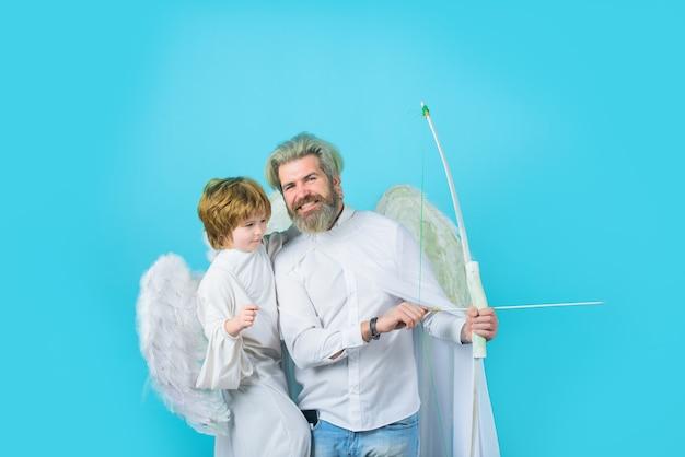 Padre feliz en traje de ángel con pequeño hijo ángel padre e hijo ángeles día del padre pequeño cupido