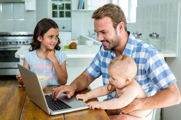 Padre feliz usando laptop mientras cuida niños