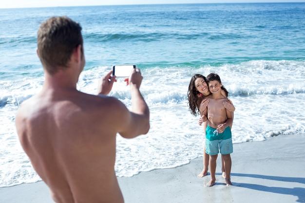 Padre fotografiando feliz esposa e hijo