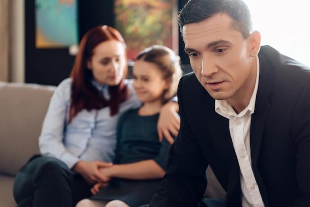 El padre frustrado en traje se sienta en el sofá al lado de esposa joven.