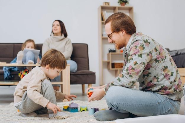 Padre en gafas e hijo adorable del niño que construye la torre de madera del constructor.