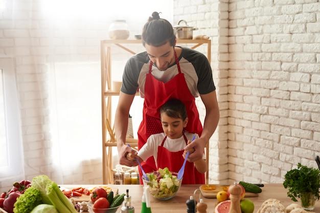 Padre helps little child para mezclar los ingredientes del plato.