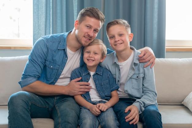 Padre y hermanos lindos sentados en el sofá