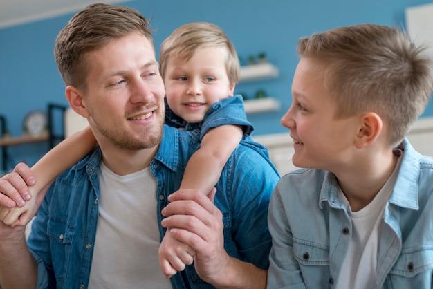 Padre con hermanos mirándose
