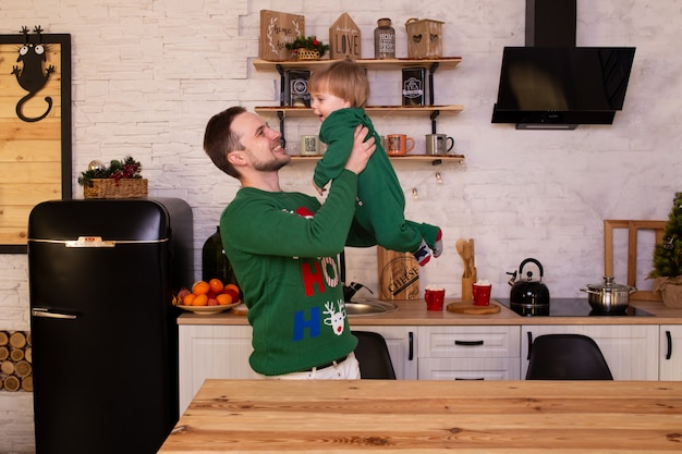 Padre higging a su hijo en la cocina de navidad en casa.