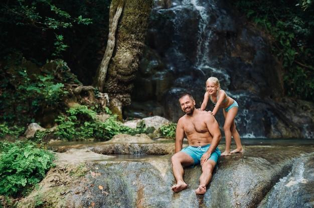 Padre con hija cerca de una cascada. viajar por la naturaleza cerca de una hermosa cascada.