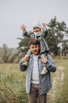 Padre con hija pequeña juntos en clima otoñal divirtiéndose