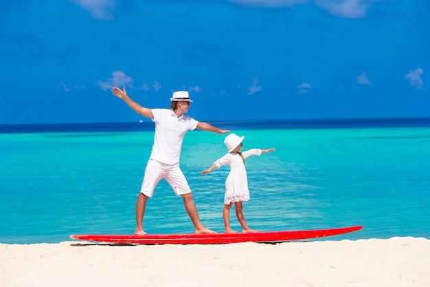 Padre con hija pequeña en la playa practicando surf