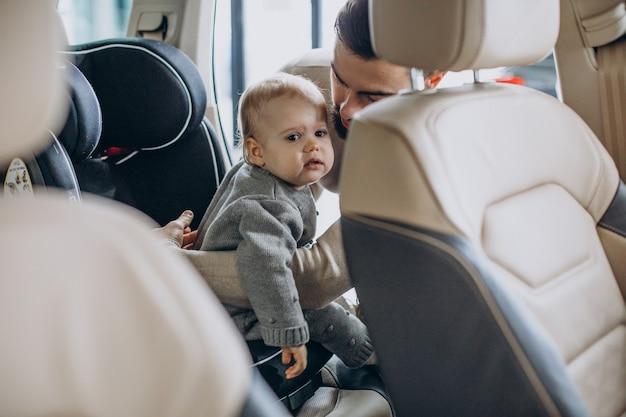 Padre con hija en una sala de exposición de automóviles