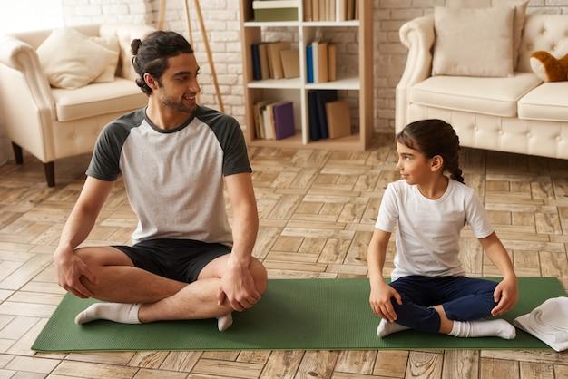 El padre y la hija sanos se sientan en lotus pose on carpet.