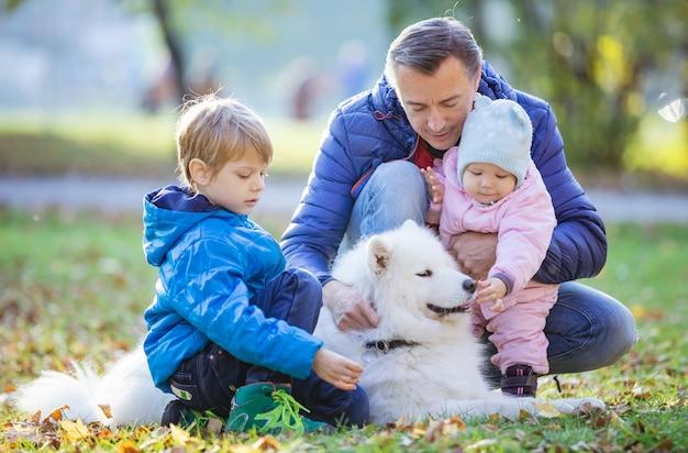 Padre con hijo e hija en edad preescolar jugando con perro samoyedo en el parque de otoño