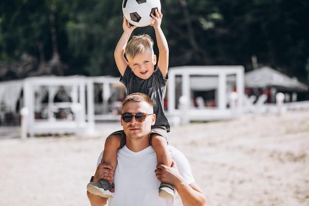 Padre con hijo jugando al fútbol en la playa.