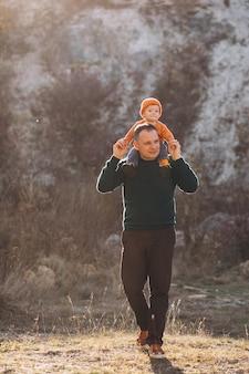 Padre con hijo en un parque de otoño