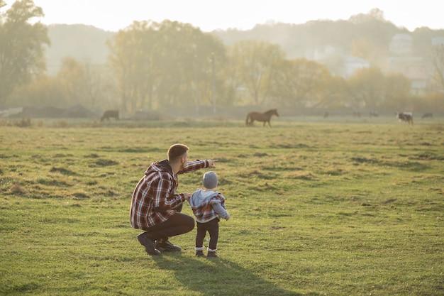 Padre con hijo pequeño caminando en un campo de mañana