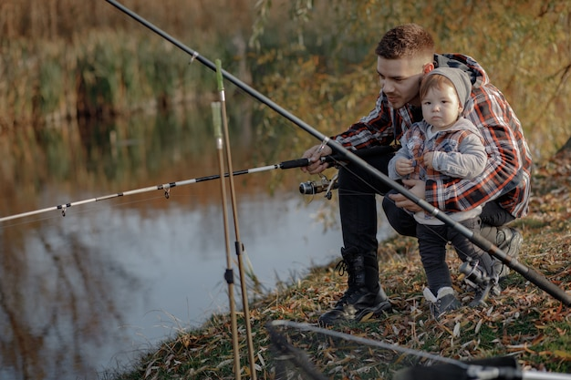 Padre con hijo pequeño cerca del río en una mañana de pesca