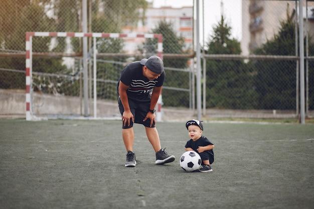 Padre con hijo pequeño jugando al fútbol