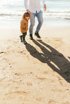 Padre con hijo en la playa de arena amarilla