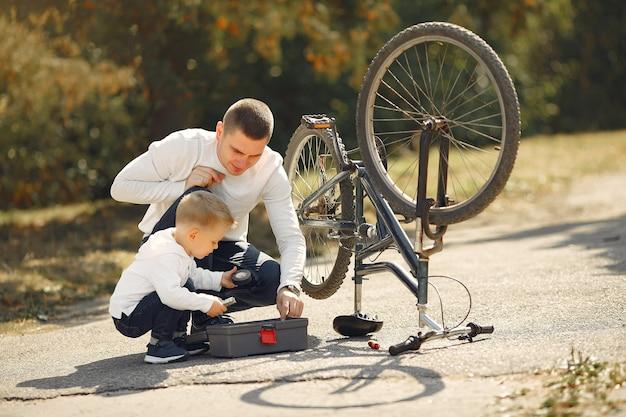 Padre con hijo repare la bicicleta en un parque