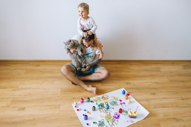 Padre con un hijo sobre sus hombros y un gato en sus manos pintado con pintura