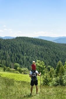 Padre con hijo sobre sus hombros de pie con el personal en el bosque verde, montañas y cielo con nubes. vista trasera