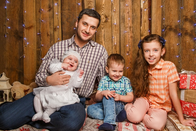Padre con hijos en una sesión de fotos navideñas