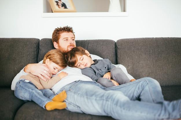 Padre con hijos siestas en sofá