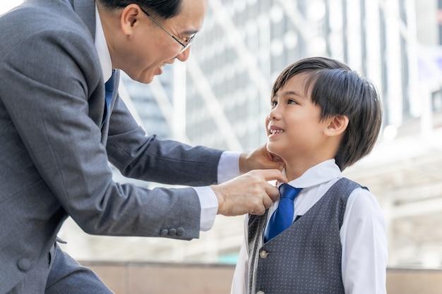 Padre hizo el cuello del traje para su hijo en el distrito de negocios urbano.