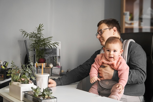 Padre del hombre con el bebé en el portador que trabaja en la oficina o en casa con la computadora en el escritorio
