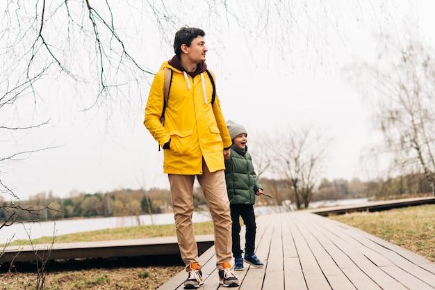 Padre en impermeable amarillo e hijo divirtiéndose en el bosque familia feliz con niño niño jugando y