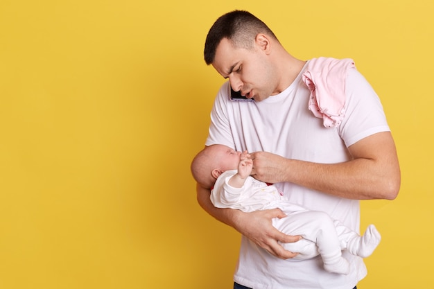 Padre joven caucásico con bebé recién nacido en manos escondidas