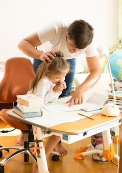 Padre joven enojado con hija haciendo los deberes