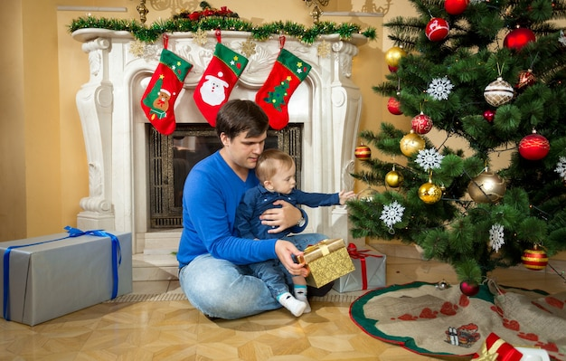 Padre joven feliz jugando con su hijo en el piso bajo el árbol de navidad