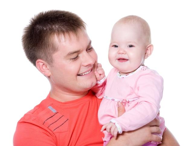 Padre joven feliz con sonrisa atractiva sosteniendo a su bebé en