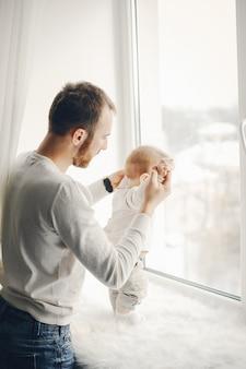 Padre joven y guapo jugando con su hijo en casa