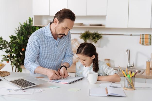 Padre joven y guapo de pie detrás del mostrador de la cocina y mostrando a su hija cómo medir la distancia con un par de brújulas mientras ella mira fijamente