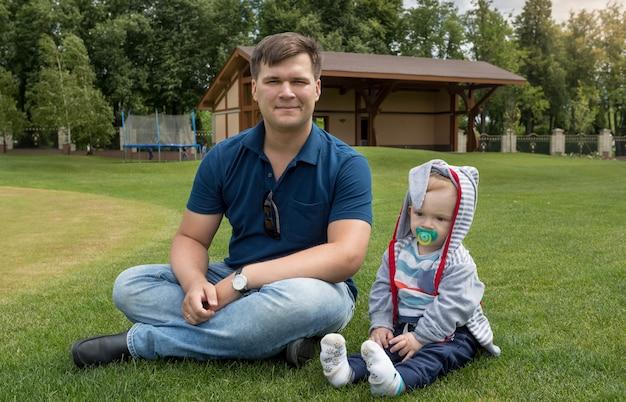 Padre joven guapo sentado con su adorable hijo de 9 meses sobre el césped en el parque
