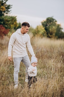 Padre joven con hijo pequeño en el campo