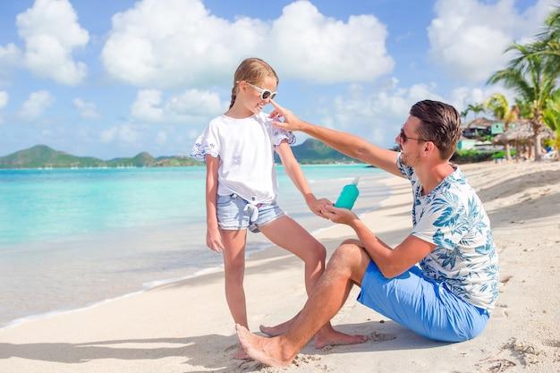 Padre joven que aplica la crema del sol a la nariz de la hija en la playa. proteccion solar