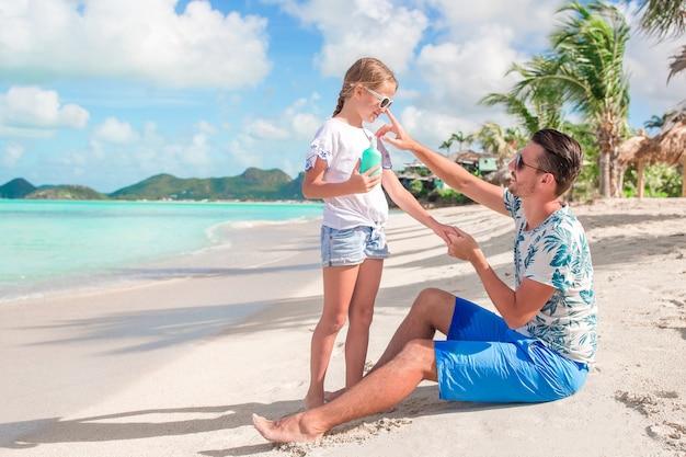 Padre joven que aplica la crema solar a la nariz de la hija en la playa. proteccion solar