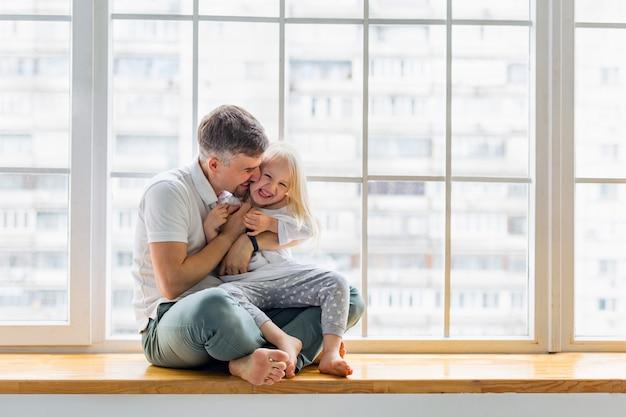 Padre joven que ríe con la pequeña hija mientras que se sienta delante de ventana. feliz papá abraza a una linda chica mientras se divierte juntos