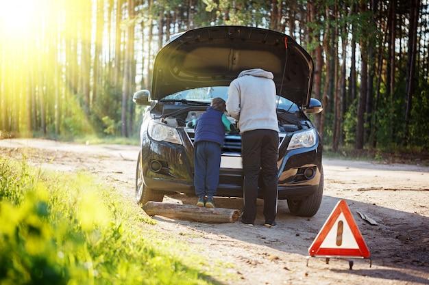 Padre joven y su pequeño hijo reparando el auto juntos en un día cálido