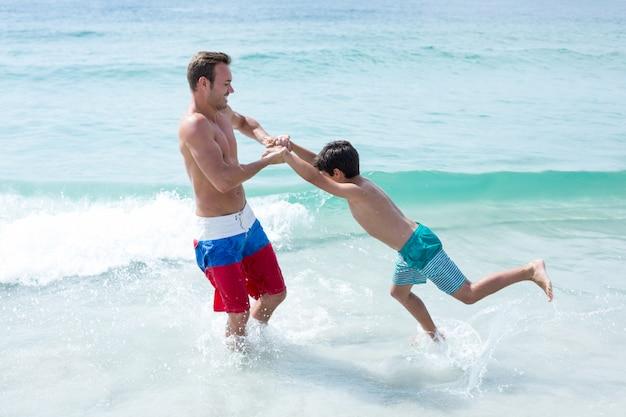 Padre jugando con hijo en la playa