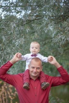 Padre jugando con el pequeño hijo en la naturaleza. concepto de familia feliz
