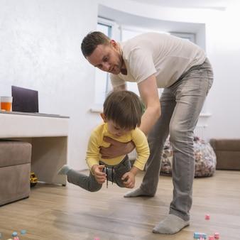 Padre jugando y sosteniendo a su hijo