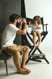 Padre jugando con su hijo pequeño en su sala de estar en casa. papá joven divirtiéndose con sus hijos en vacaciones o fines de semana