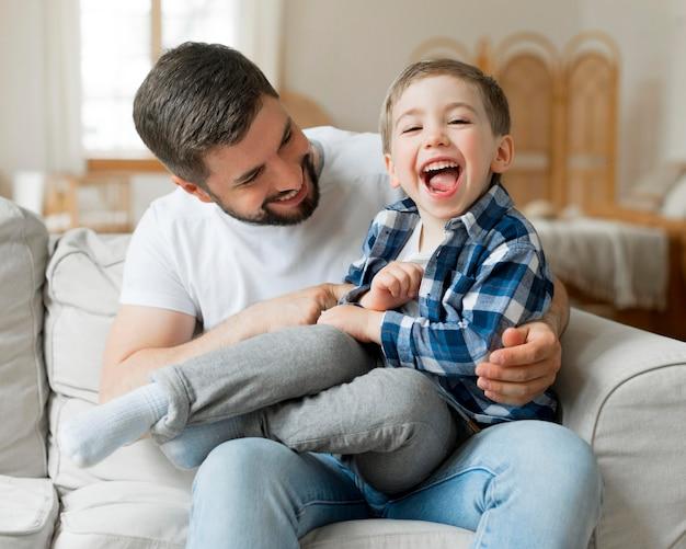 Padre jugando con su hijo en el sofá