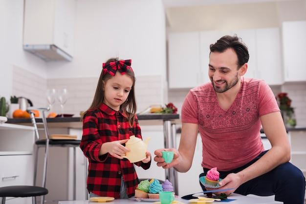 Padre jugando a las tazas con su hija